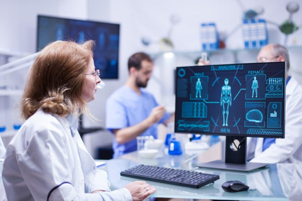 Female scientist looking at the monitor screen in research room